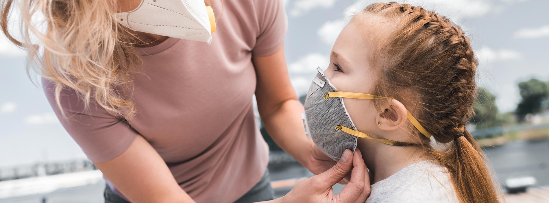 Mother is helping to her daughter to wear a mask